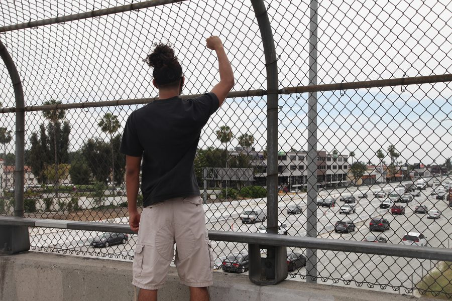 A demonstrator looks out onto the Interstate-10 Freeway, in Covina, California on June 1, 2020, a fist raised in protest of the murder of George Floyd. Photo credit: Abraham Navarro/SAC.Media.