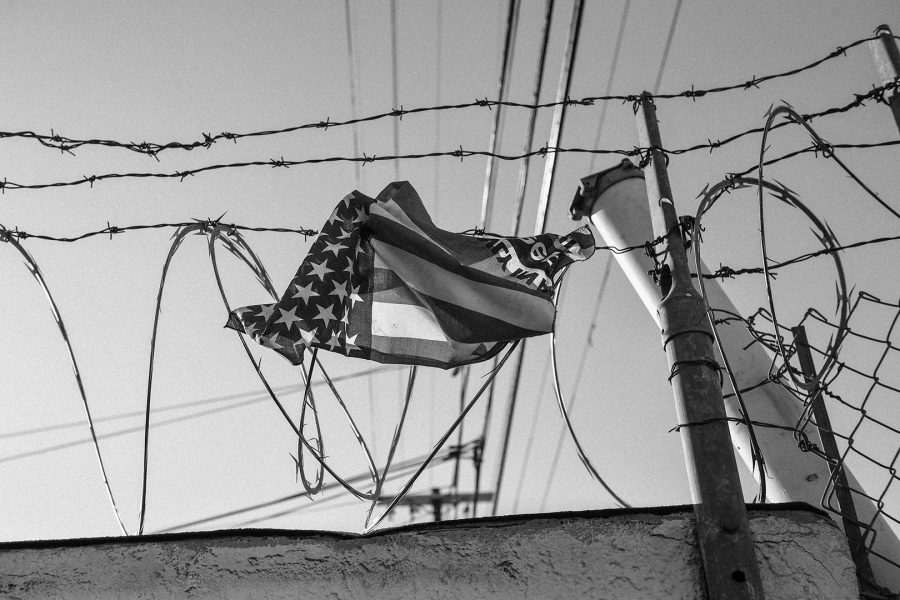 An American flag with words printed on it entangled in barbed wire above a wall. Highland Park, a predominantly Latino community in recent years has been subject to gentrification. Photo Credit: Pablo Unzueta