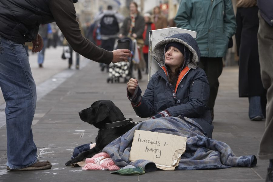 Person+giving+cup+to+homeless+woman