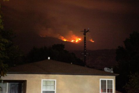 The bobcat fire rages behind a home in the hills above Monrovia, California on Sept. 9, 2020. Ashes can be see floating down and coating cars in a fine layer of grey dust. Smoke fills the air and can be seen in a dull gray haze beneath street lights. Photo credit: Abraham Navarro/SAC.Media