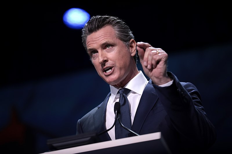 Governor Gavin Newsom speaking with attendees at the 2019 California Democratic Party State Convention at the George R. Moscone Convention Center in San Francisco, California. Posted on Wikimedia Commons by user Gage.