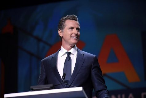 Governor Gavin Newsom speaking with attendees at the 2019 California Democratic Party State Convention at the George R. Moscone Convention Center in San Francisco, California. Posted on Wikimedia Commons by user Gage Skidmore.