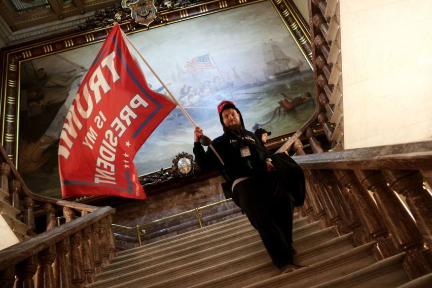 A Trump supporter holds a Trump flag inside the US Capitol Building near the Senate Chamber on January 06, 2021 in Washington, DC when rioters stormed the Capitol.