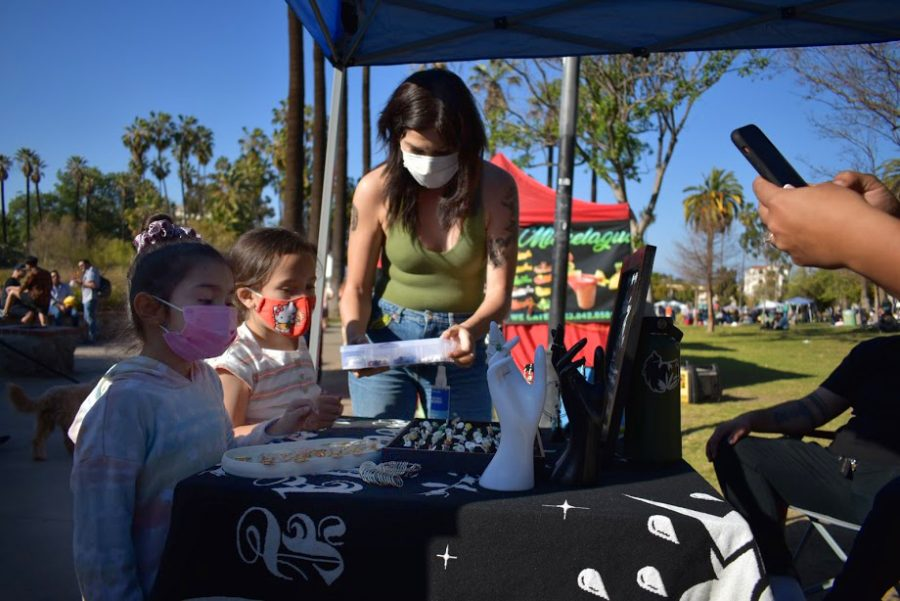 Local arts and craft vendors have clients that vary in all ages. Alexandra Gualito, is featured with her two newest customers, in Echo Park.