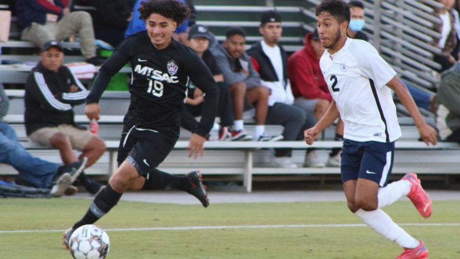 Eddie Cabrera (19) is running down field to get closer to the a scoring position but Brandon Galindo (2) is right behind him and is not going to let him through.